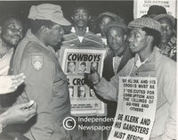 A policeman talks to a protester while others look on, Cape Town